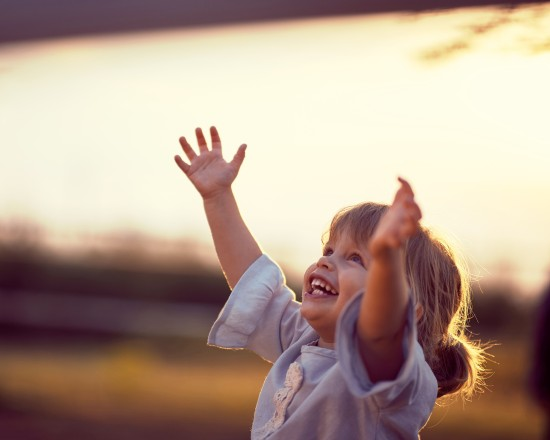 Little girl sis smiling at sunset