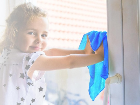 Small girl cleaning window