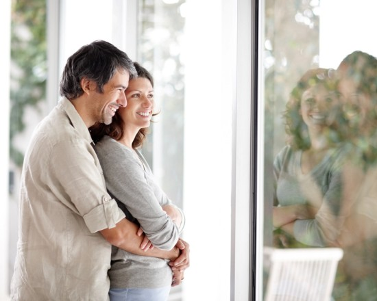 Couple standing in front of a window